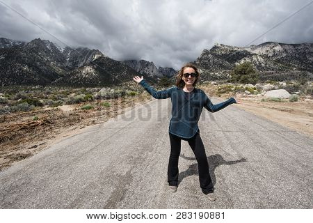An Adult Female Stands In The Middle Of Whitney Portal Road, In Lone Pine California. This Unpaved R