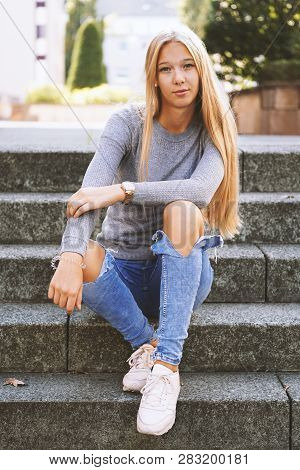 Teenage Girl With Long Blond Hair And Distressed Jeans Sitting On Steps Outside - Urban Lifestyle Or
