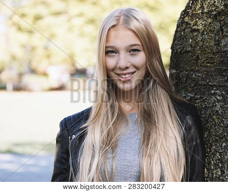 Teenage Woman With Long Blond Hair And Leather Jacket Leaning Against Tree On A Sunny Day In Spring