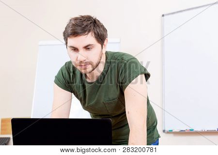 Portrait Of Informal Male Teacher In Classroom On Lesson. Creative Young Man Teaches Online On The C