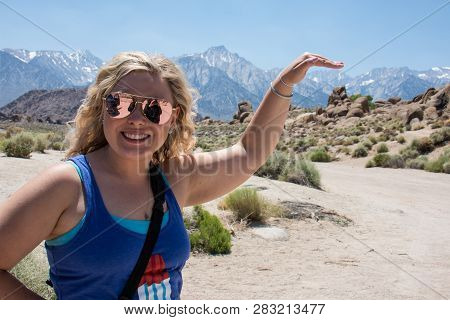 Forced Perspective View Of A Blonde Woman Apprearing To Touch Mt. Whitney In The Alabama Hills Of Ca