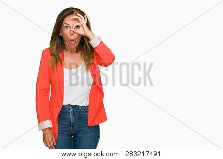 Beautiful middle age business adult woman over isolated background doing ok gesture shocked with surprised face, eye looking through fingers. Unbelieving expression.