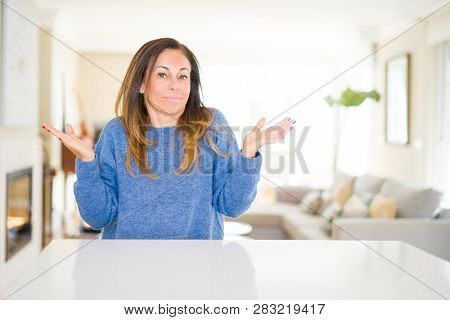 Beautiful middle age woman at home clueless and confused expression with arms and hands raised. Doubt concept.