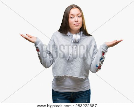 Young beautiful caucasian student woman wearing headphones over isolated background clueless and confused expression with arms and hands raised. Doubt concept.