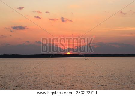 Beautiful pink sunset on the lake. Evening landscape. Beautiful clouds over the water. Clouds over the lake. The horizon at sunset. Sea, lake at sunset. The sun through clouds. The waves on the river. The lake in Russia