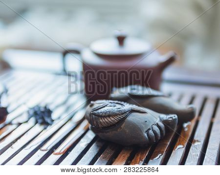 Chinese Tea Ceremony. Close Up View Of Buddha Foot Figure And Clay Teapot On Wooden Tabletop. Pu Erh