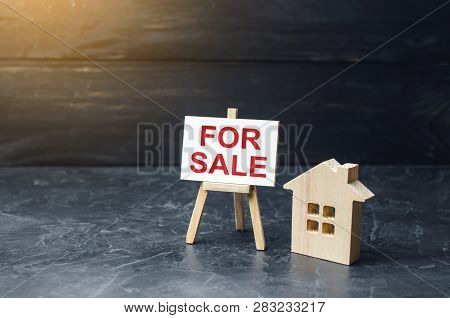 Wooden House Stand With A Sign For Sale. Selling A House Or Apartment And Property. Housing And Real