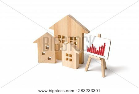 Wooden Houses With A Stand Of Graphics And Information. Growing Demand For Housing And Real Estate.