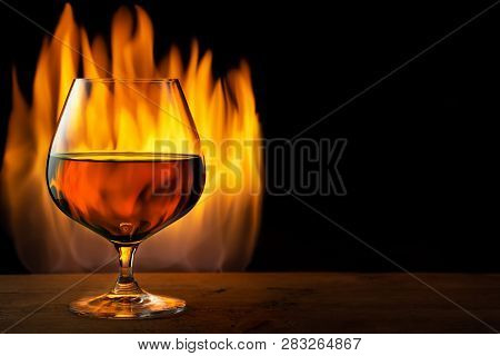 Brandy Or Cognac In Snifter Glass On Fire Background