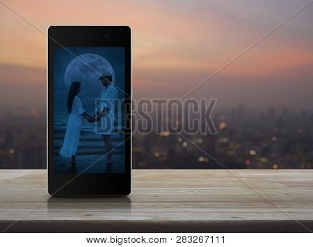Romantic Loving Couple Standing And Holding Hands Together On Modern Smart Mobile Phone Screen On Wo