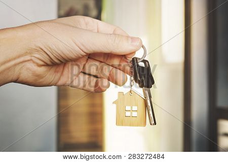 poster of House key in male hand at apartment background. house key ring. Concept of moving in new living apartment. Symbol of purchasing house. Estate investment. Buy property. real estate transaction
