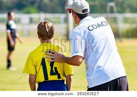 Back View Of Male Football Coach In White Coach Shirt At An Outdoor Sport Field Sending His Young Bo