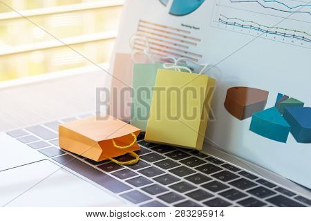 Colorful Shopping Bag And Marketing Graph Report Behind Its On Laptop Keyboard. Consumer Can Buy Pro