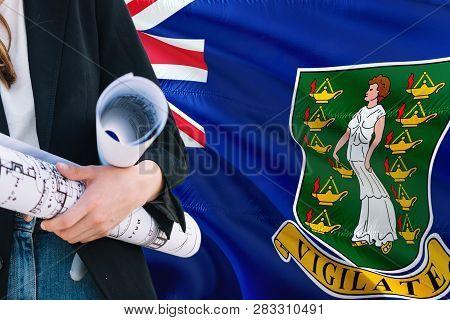 Architect Woman Holding Blueprint Against British Virgin Islands Waving Flag Background. Constructio