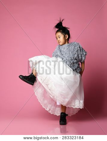 Young Asian Girl Kid In Long White Skirt, Grey Fluffy Sweater And Black Boots Step On Vigorously On