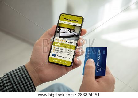 Male Hands Holding Phone With App Hotel Booking On The Screen And A Credit Card