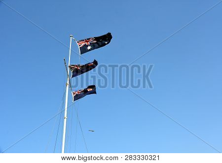 Australian Flags Waving In The Wind. Flags Of Australia Waving In The Wind Against White Cloudy Blue
