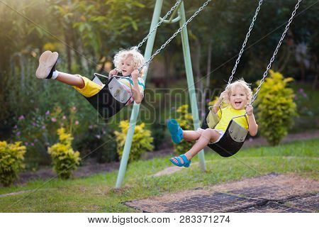 Child Swinging On Playground. Kids Swing.