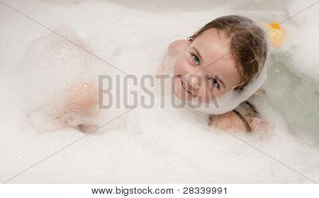 Little girl having fun in a bathtub full of soap foam.