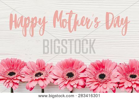 Happy Mother's Day Text Sign At Pink Gerbera On White Wooden Background, Flat Lay. Floral Greeting C