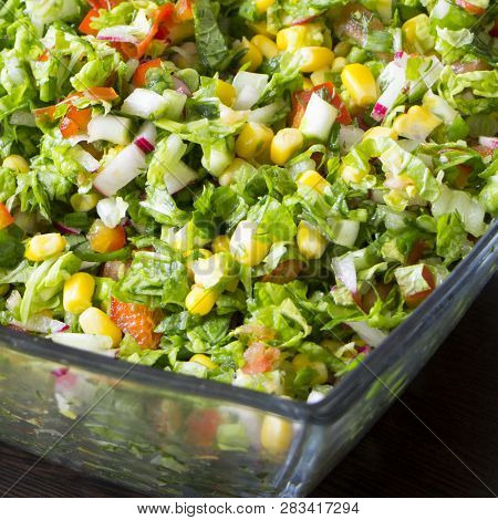 Fresh Vegetarian Salad With Greens, Corn, Onion, Dill, Parsley, Radishes, Sweet Red Pepper And Tomat