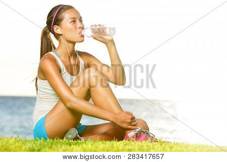 Fitness woman drinking water after running training workout outside by ocean sea. Beautiful sweaty fit fitness model sitting in warm sun light enjoying water bottle listening to music in earphones.