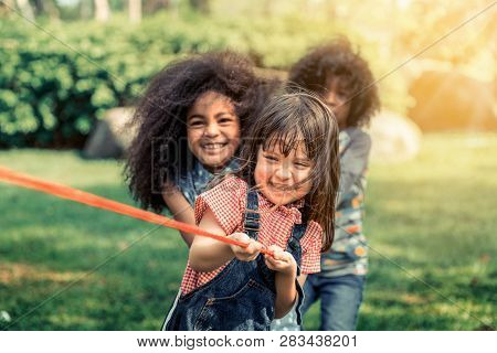 Happy Children Playing Tug Of War And Having Fun During Summer Camping In The Park. Children Recreat