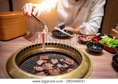 Asian Man Using Kitchen Tongs Grilling Beef And Bacon On Grill Plate. Eating Korean Barbecue Buffet
