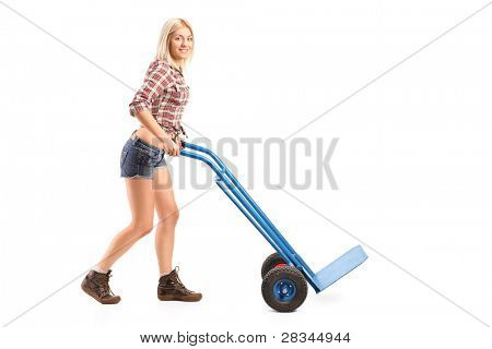 Full length portrait of a female manual worker pushing an empty handtruck isolated on white background