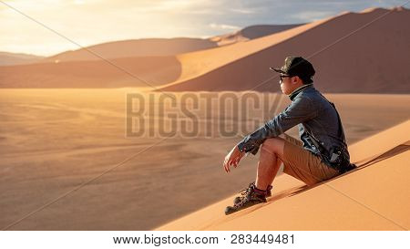 Young Asian Man Traveler And Photographer Looking At Scenery While Sitting On Sand Dune In Namib Des