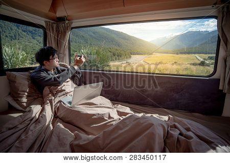 Asian Man Traveler Enjoy Taking Photo Of Mountain Scenery Through The Window By Smartphone While Sta