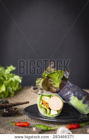 Salad Rolls On Black Plate Placed On A Sack With Chilli And Garlic Placed In Front Of There Is Chops