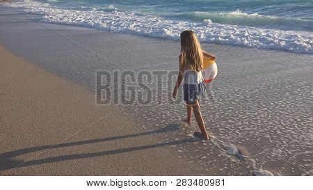 Child Playing On Beach At Sunset, Happy Kid Walking In Sea Waves Girl On Seaside
