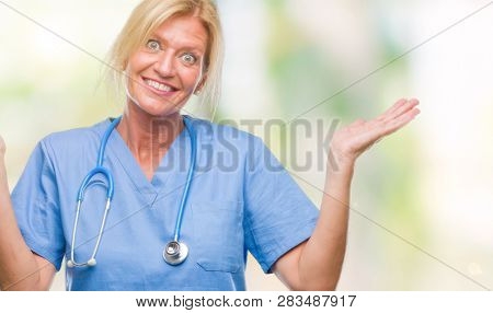 Middle age blonde nurse surgeon doctor woman over isolated background clueless and confused expression with arms and hands raised. Doubt concept.