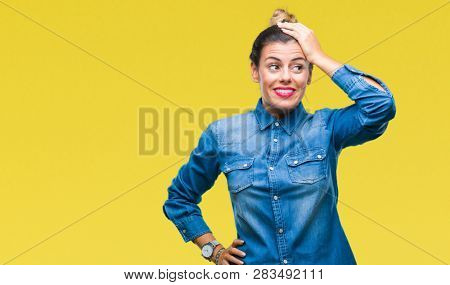 Young beautiful woman over isolated background confuse and wonder about question. Uncertain with doubt, thinking with hand on head. Pensive concept.
