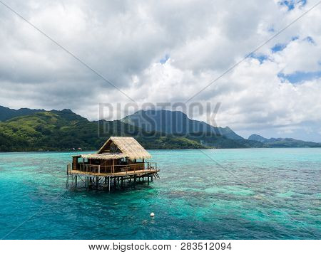 Overwater Bungalow Of Black Pearl Farmers. Blue Azure Turquoise Lagoon With Corals. Emerald Raiatea
