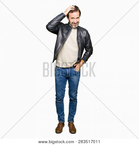 Middle age handsome man wearing black leather jacket confuse and wonder about question. Uncertain with doubt, thinking with hand on head. Pensive concept.