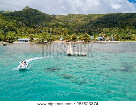 Raiatea, French Polynesia - Nov 16 2017: Tourists Riding High Speed Jet Boat In A Stunning Azure Blu