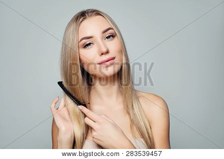 Beautiful blonde woman with long healthy straight hair combing hair. Haircare concept. Girl combs hair. poster