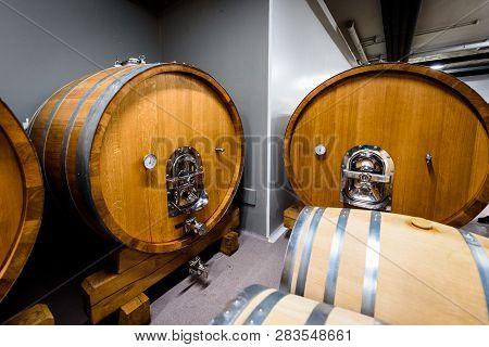 Wooden Wine Barrels Stacked In Modern Winery Cellar In Spain.