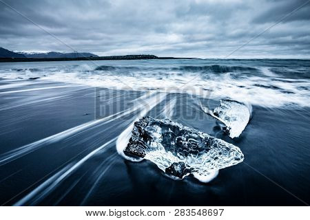 Incredible piece of the iceberg sparkle on black sand. Location Jokulsarlon lagoon, Diamond beach, Vatnajokull national park, Iceland, Europe. Popular tourist attraction. Discover the beauty of earth.