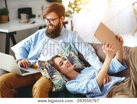Happy Family Couple Relaxing At Home With Laptop And Tablet