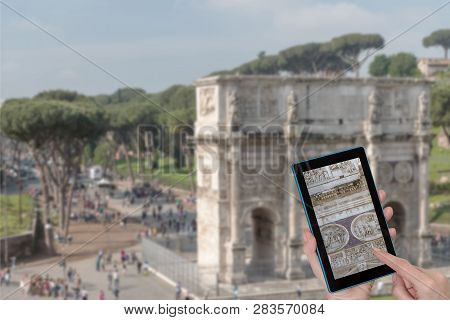 Female Finger Touching Tablet With Detail Of Arch Of Constantine In Rome (italy). Intentionally Blur