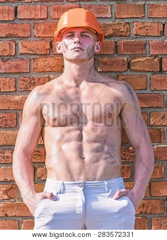 Builder With Muscular Torso And Helmet, Brick Wall On Background. Hard Worker Concept. Builder With