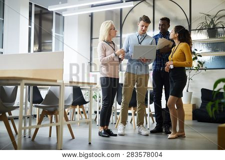 Group Of Confident Multiethnic Colleagues In Casual Clothing Standing In Coworking Space And Analyzi