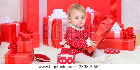 Little Baby Play Near Pile Of Wrapped Red Gift Boxes. Gifts For Child First Christmas. My First Chri
