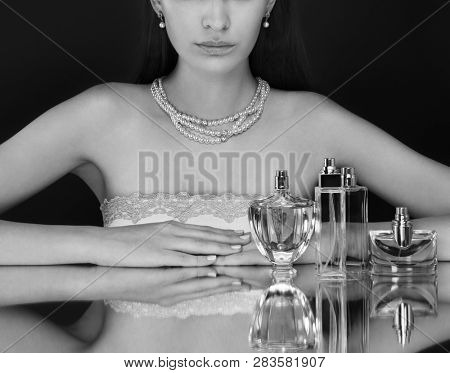 Beautiful woman and collection of perfumes bottles on dark background. Black and white.