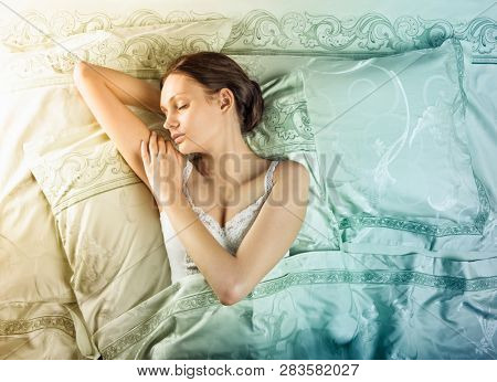 Beautiful young woman sleeping in luxury bed. Bed is made with linen embroidered percale. Space for text.