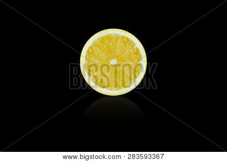 View Of A Lemon Slice Mirrored On Black Background. . Close-up Of A Yellow Juicy Lemon Slice.