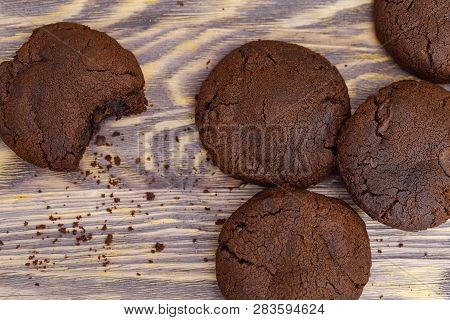 Chocolate Cookies Close Up On Wooden Background. Dark Brown Round Cookies. Top View. Copy Space.